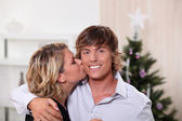 Une jeune femme embrasser un jeune homme devant un arbre de noël — Photo