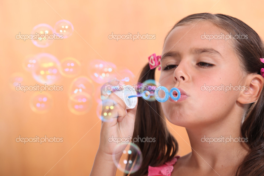Young girl blowing bubbles — Stock Photo #9163121