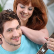 Young couple with a guitar at home — Stock Photo #9170395