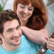 Young couple with a guitar at home — Stock Photo