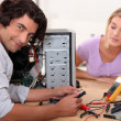 Stock Photo: Mid long hair mis repairing computer in front of blonde woman