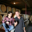 Winemakers drinking wine in a winery - Stock Photo