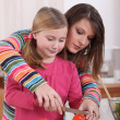 Woman showing her daughter how to cut a tomato — Stock Photo
