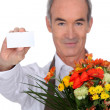 Florist showing business card - Stock Photo
