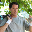 Sporty man with bottle of water - Stock Photo