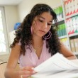 Teenage girl studying in the library — Stock Photo