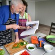 Elderly couple preparing a meal with the help of a cookbook — Stock Photo