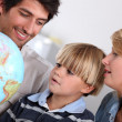 Parents and son looking at a globe — Stock Photo #9171598