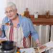 Elderly woman cooking dinner with the help of a recipe — Stock Photo