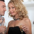 Stock Photo: Flirtatious couple drinking champagne at home