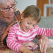 Stock Photo: Grandmand granddaughter playing game
