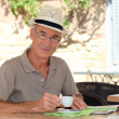 Senior citizen sipping his coffee in terrace cafe — Stock Photo