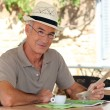 Stock Photo: Peaceful retiree sitting at table