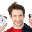 Man holding alarm clock and mobile telephone — Stock Photo #9172754