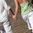 Couple holding hands while walking along the seashore - Stock Photo