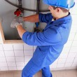 Plumber using a wrench on some large water pipes — Stock Photo #9172944
