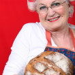 Senior woman with curlers in her hair holding fresh baked bread — Stock Photo #9173144