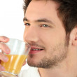 Man drinking a glass of orange juice — Stock Photo #9173225
