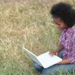 Young woman using a laptop in a field — Stock Photo