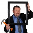 Man in a suit with a picture frame and hammer - Stock fotografie