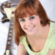 Young woman sitting near a guitar — Stock Photo #9173933