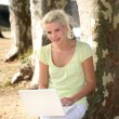 Young woman working on her laptop in the park — Stock Photo