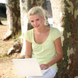 Young woman working on her laptop in the park — Stock Photo #9178011