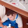 Plumber working in the kitchen — Stock Photo