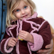 Stock Photo: Young girl wearing a coat and holding a lolly