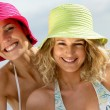 Two female friends having fun at the beach - Stock Photo