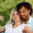 Mixed race couple relaxing in park - Stock Photo