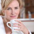 A young woman wearing a dressing gown, holding a mug and looking at us. — Stock Photo #9179083