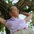 Woman leaning against a tree — Stock Photo