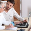 Young man helping senior woman buy online — Stock Photo #9179690