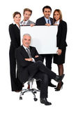 Four young executives holding a blank presentation board behind their boss — Stock Photo
