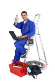 Technician with laptop and cellphone leaning on a ladder — Stock Photo