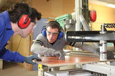 Craftsman and his apprentice working together — Stock Photo