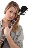 Blond teenage girl posing with guitar — Stock Photo