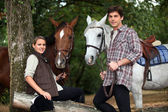 Young couple with two horses — Stock Photo