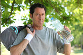 Sporty man with bottle of water — Stock Photo