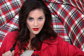 Attractive brunette holding umbrella — Stock Photo