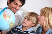 Parents and son looking at a globe — Stock Photo