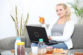 Woman using a laptop at breakfast time — Stock Photo