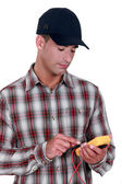 Young electrician wearing cap using tester — Stock Photo
