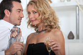 Flirtatious couple drinking champagne at home — Stock Photo