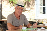 Peaceful retiree sitting at a table — Stock Photo