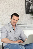 Smiling man with laptop indoors — Stock Photo