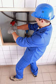 Plumber using a wrench on some large water pipes — Stock Photo
