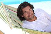 Hamak yüzme havuzu yanında oturan adam — Stok fotoğraf