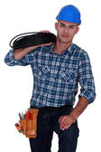 Electrician carrying spool of wiring — Stock Photo